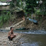 Iban tribesman in front of their long house